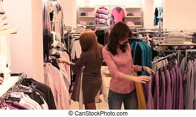 Choosing a sweater - Happy friends doing shopping and...