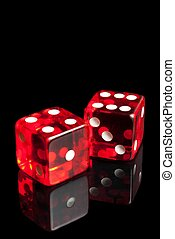 red dice on transparent black background - detail of red...