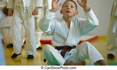 karate class - group of children in gym playing before the...