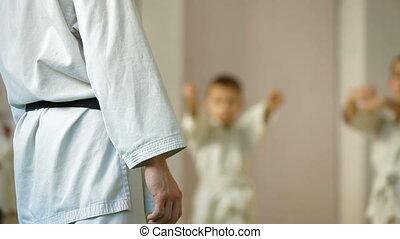 coach at the gym teaches children Martial Art