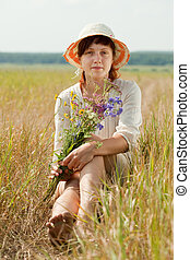 girl in summer field - Sitting girl with flowers posy in...