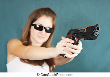 girl aiming a black gun - Long-haired teen girl aiming a...