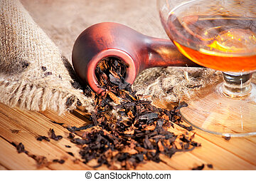 Glass of cognac and pipe with tobacco on wooden table with...