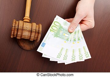 Hand showing money near justice gavel