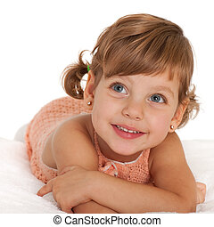 Happy little girl on the bedspread - A happy little girl is...
