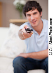 Remote being used by man on the sofa - Remote being used by...