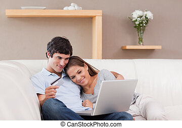 Happy couple booking holiday online - Happy young couple...