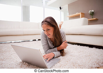 Woman lying with laptop on the floor