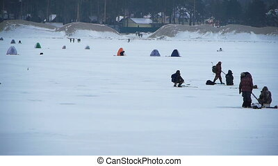 Ice Fishing - many fishermen on an ice river