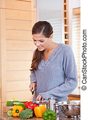 Woman in the kitchen slicing vegetables