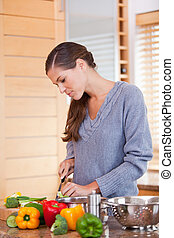 Woman in the kitchen preparing vegetables - Young woman in...