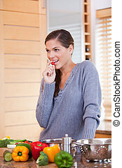 Woman snacking a small tomato while preparing dinner