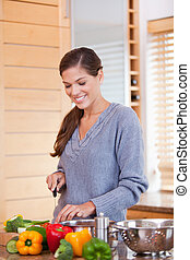 Smiling woman in the kitchen slicing vegetables