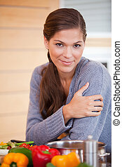 Woman leaning against the kitchen counter - Young woman...