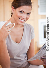 Smiling woman reading the news while drinking coffee