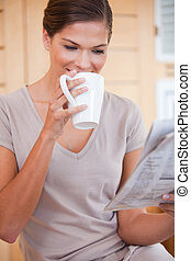 Woman taking a sip of coffee while reading newspaper