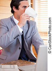 Businessman enjoying a cup of coffee in the kitchen