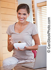 Smiling woman eating cereals next to her laptop