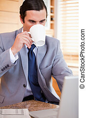 Businessman taking a sip of coffee next to his laptop