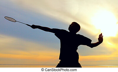 man playing badminton - silhouette of badminton player...