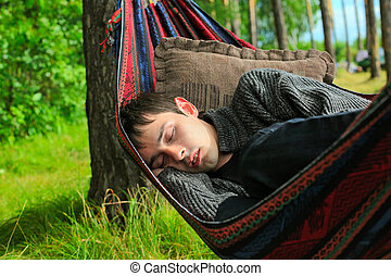 young man sleeping in the hammock on the nature