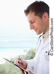 Side view of doctor taking notes