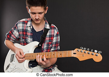 Young male playing electric guitar - Photo of a teenage male...