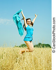 Jumping girl on wheat field in summer