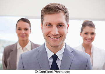 Sales manager standing with his team behind him