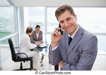 Sales manager on the phone with his team sitting behind him