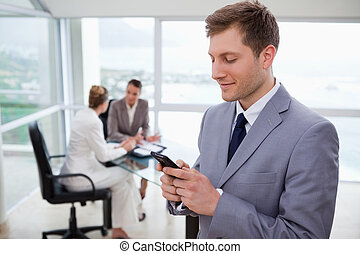 Sales manager writing text message with his team sitting...