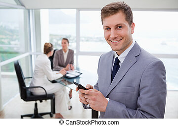 Sales manager holding cellphone with his team sitting behind...