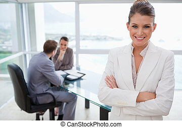 Smiling marketing manager standing in conference room with...