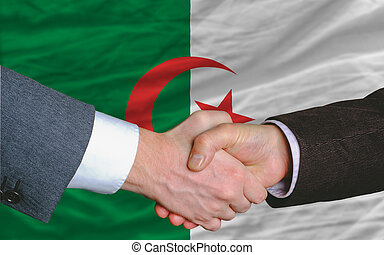 businessmen handshake after good deal in front of algeria...