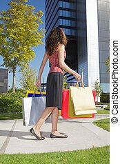 shopper woman down skyscrapers - brunette woman with...