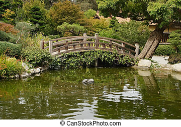 A small pond and a decorative wooden bridge in the Japanese...