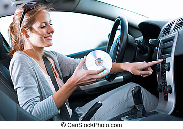 Young female driver playing music in the car changing CDs