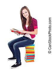 Read every day - Young girl reading while sitting on a pile...