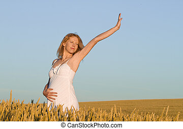 pregnant woman in white dress relaxing outdoors