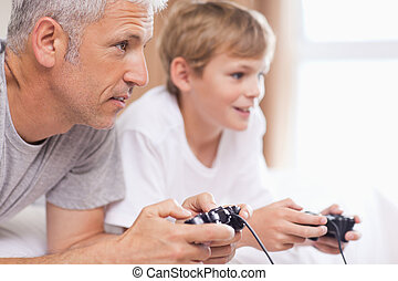 Father playing video games with his young son