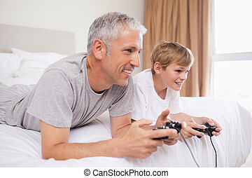 Happy father and his son playing video games
