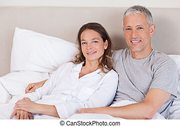 Couple lying on a bed in the morning