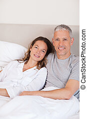 Portrait of a couple lying on a bed while looking at the...