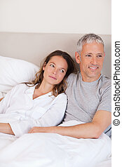 Portrait of a happy couple lying on a bed while looking away...