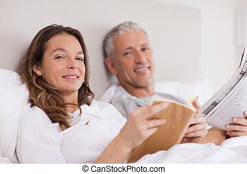 Smiling woman reading a book while her husband is reading the news in their bedroom