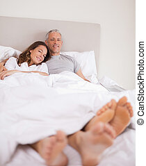 Portrait of a lovely couple lying on their bed while looking...