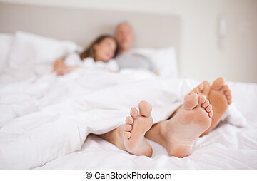 Lovely couple lying in a bed with the camera focus on their...