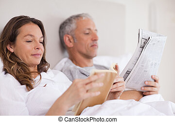 Woman reading a book while her husband is reading the news...