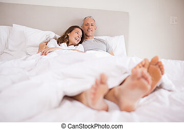 Charming couple lying in a bed