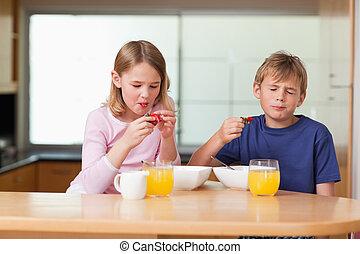 Siblings eating strawberries for breakfast